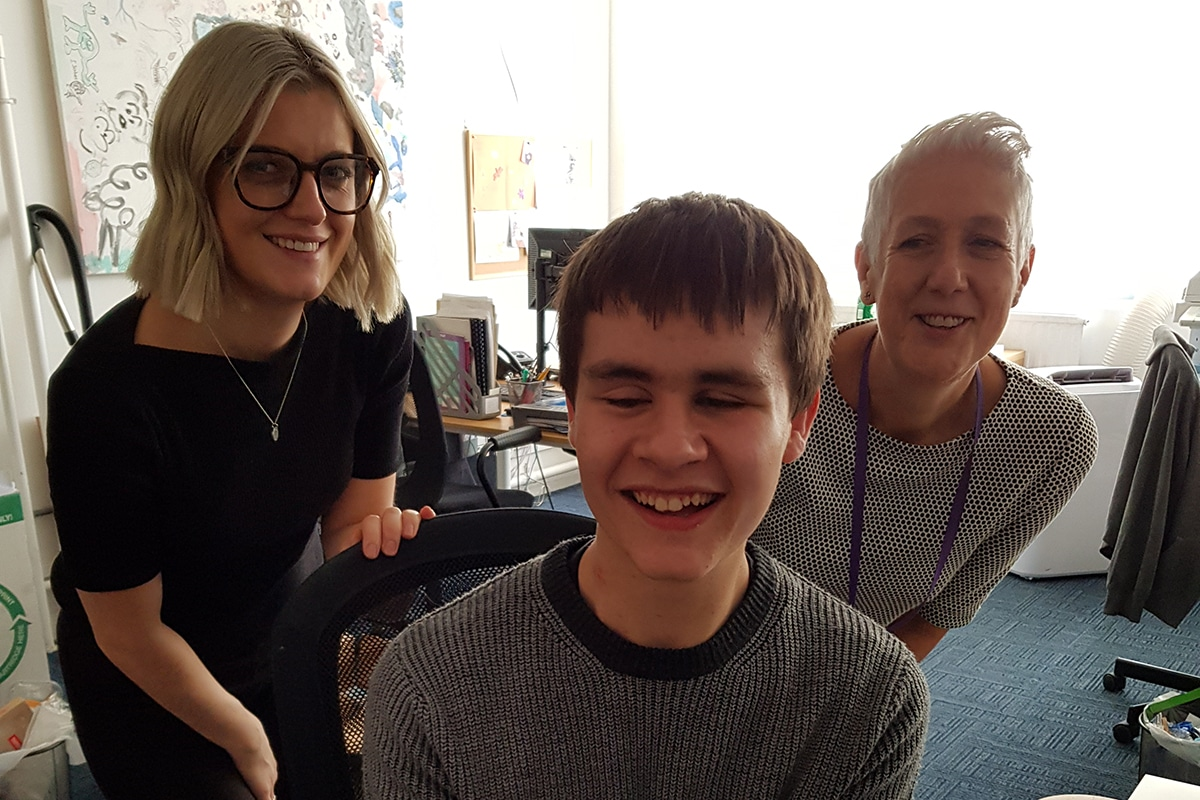 Photo of Kelsey celebrating his exam results in the CHECT office with Hayley and Diane